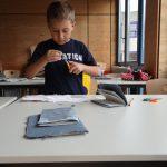 konzentriert-arbeiten-die-kinder-an-ihren-vielseitigen-moeglichkeiten-mit-dem-papier-hier-entsteht-ein-bucheinband-die-buecher-wurden-uebrigens-on-hand-mit-nadel-und-faden-gebunden